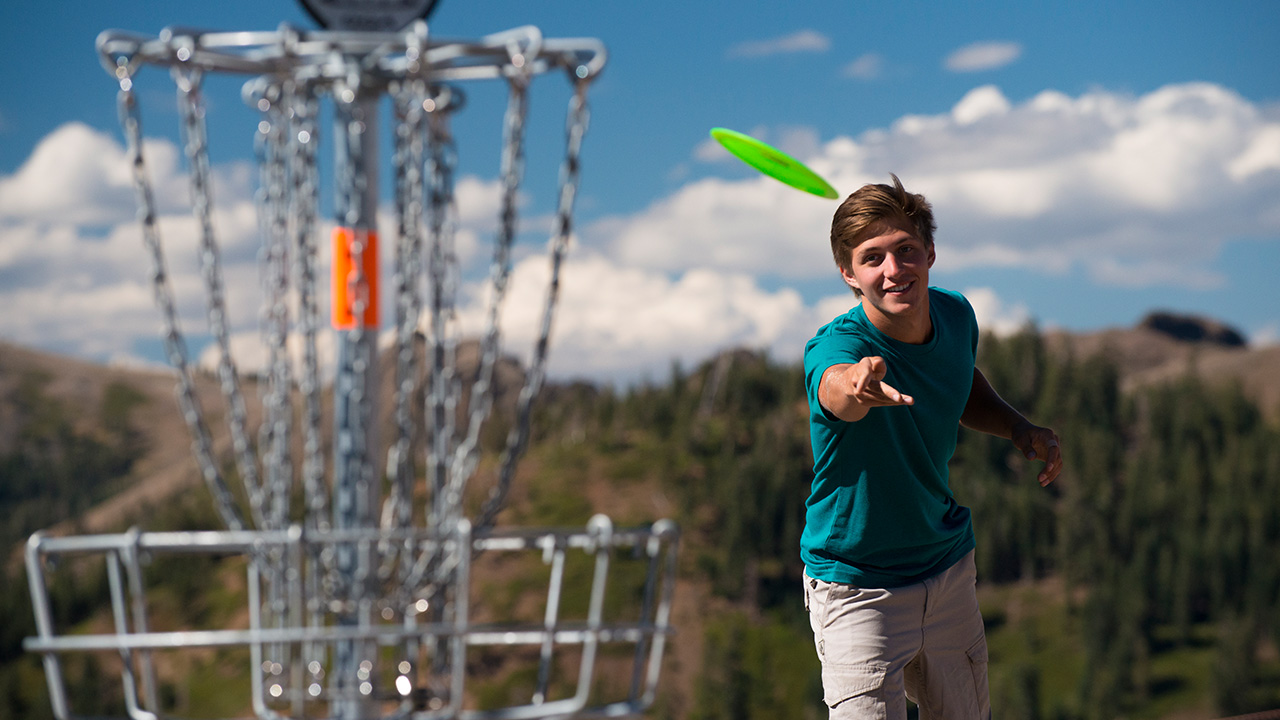 Teen boy playing disc golf