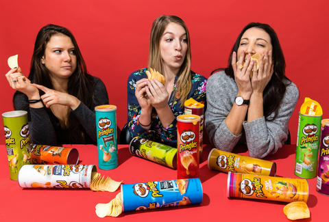 Three young women eating different flavored Pringles.