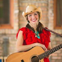Woman in a cowboy hat holding a guitar